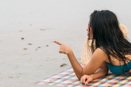 Thai woman in Bikini with Sunglasses laying on beach point finger