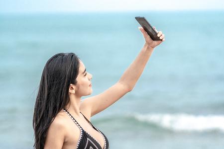 Thai Woman in black bikini waling on the beach and selfie with mobilephone