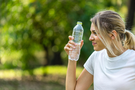 Beautiful Caucasian woman in white T-shirt  holding water bottle  and smiling With green blur background Banco de Imagens