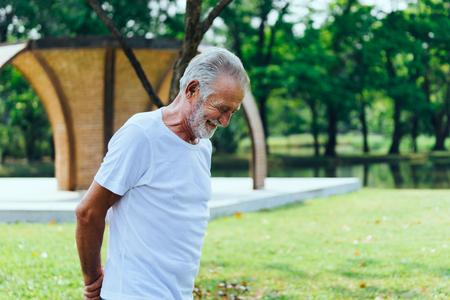 Caucasian elderly man  in white T-shirt  walking and smiling having good mood in the Green park Banco de Imagens