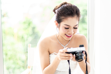 Thai Bride in White dress looking pictures from camera of wedding photographer