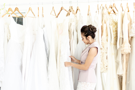 Asian woman choose wedding dresses on hanger in Wedding shop Boutique