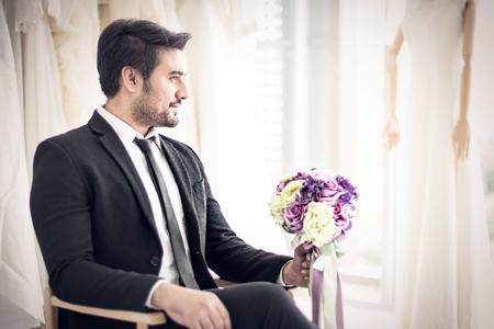 Groom men waiting for Bride with Bouquet in his hand in wedding dress shop Banco de Imagens