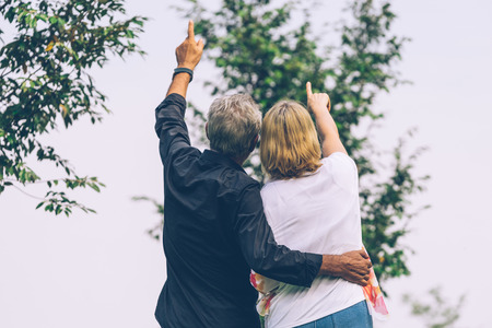 Back of Elderly couple standing together looking to the sky