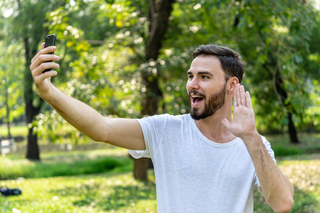 caucasion man in White T-shirt selfie with his smartphone in public park