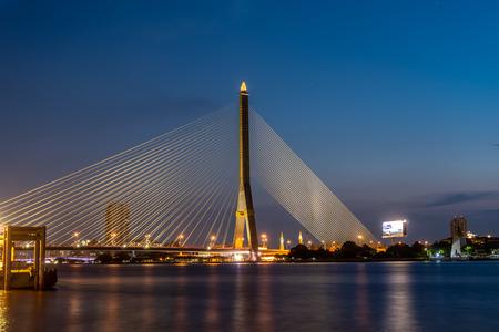 Rama 8 Suspension Bridge over smooth Chao Phraya River in Evening Twilight
