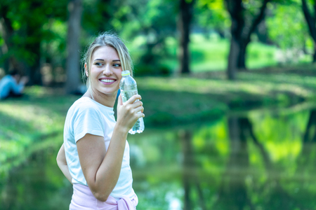 Woman smiling in White T-shirt rest and holding Pet Plastic bottle in Public park