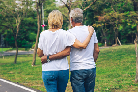 Elderly couple walking together on path of public park in Vintage tone Banco de Imagens