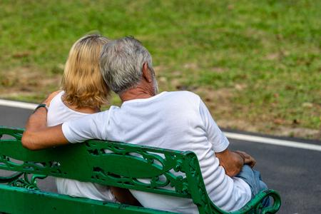 Elderly couple sitting holding together on bench in public park Banco de Imagens