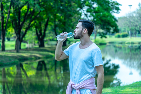 Caucasion man thirsty and drinking water from pet bottle in public park after exercise