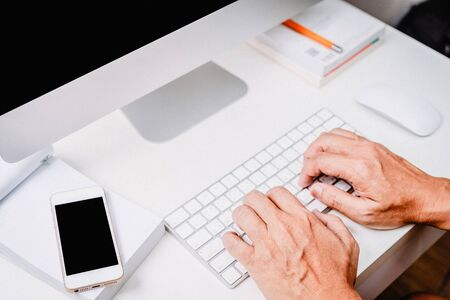 hand typing white computer keyboard of desktop computer on White desk modern style office Banco de Imagens