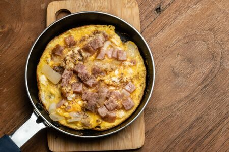 Omlet fried egg in pan on wooden table from Top view Banco de Imagens