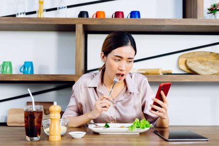 Asian Woman eating food and reading news from mobile phone sitting in dining room