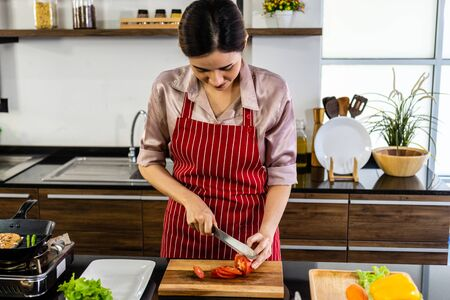 Asian Woman cook is cutting tomatoes in modern kitchen with smiling face