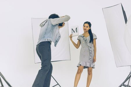Asian Photographer shooting with Asian female model in Studio with studio strobe