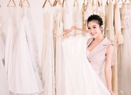 Asian Beautiful bride Smiling choosing a wedding dress in the boutique.