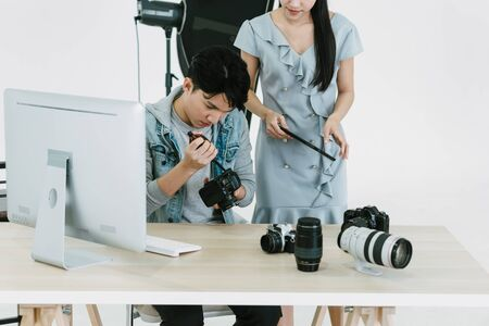 Asian Photographer cleaning blowing the dust from his camera on the desk