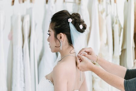 The Asian bride is dressed to attend the wedding ceremony wearing a diamond necklace with smiling beautiful face Banque d'images