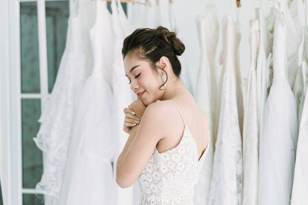 The Asian bride is trying on the wedding dress to dress up to attend the ceremony. Banque d'images