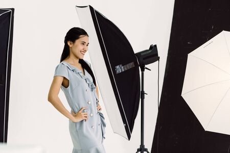 Asian Photographer shooting with female model in Studio with studio strobe