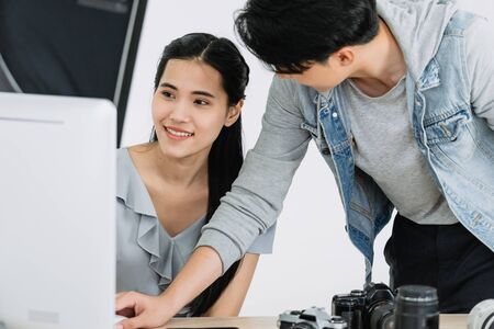 Model and Photographer looking pictures from monitors computer and choosing the right pictures
