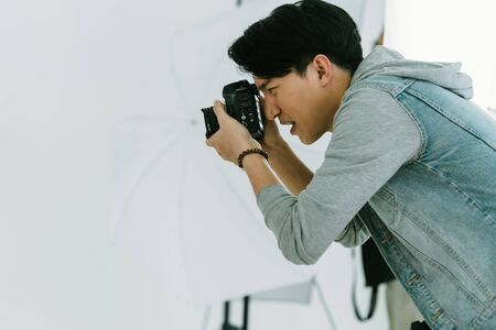 Asian Photographer focusing and shooting with model in Studio with studio strobe