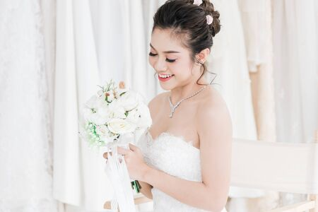 Beautiful asian bride in a wedding dress Holding a beautiful bouquet of flowers with a smiling face in wedding shop