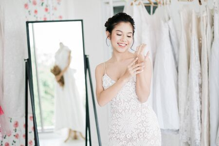 The Asian bride is trying on the wedding dress to dress up to attend the ceremony and show her wedding ring