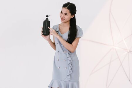 Asian girl model showing bottles of goods while shooting fashion, advertising products in the studio with white background