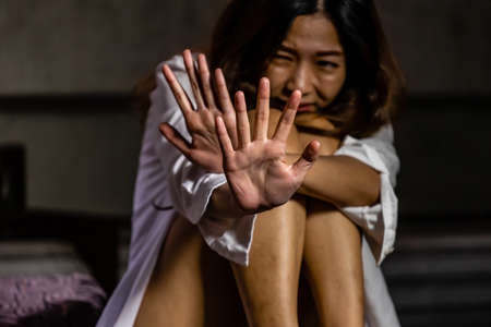 An Asian woman raises her hand in fear of being attacked. Afraid of being raped Sexual crime Harassment The dangers of society, violence, sexual oppression.