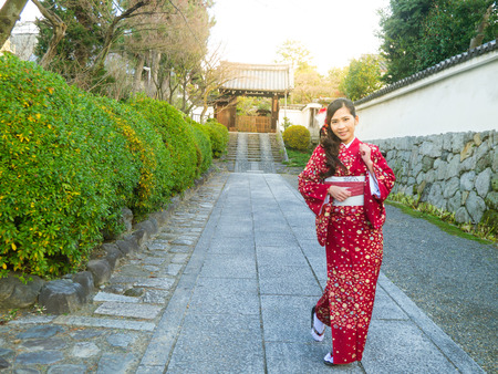 Asian woman in red light Kimono or Yukata on some street in Kyoto with evening sunlight Stock Photo