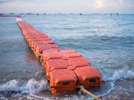 Floating wave breaker and rope on beach Imagens