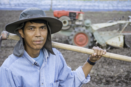 Asian farmer holding plow in agriculture field with cultivate machine in background Stock Photo