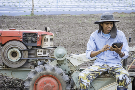Asian farmer with machine using tablet in agriculture field