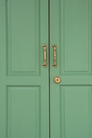 Green dřevěné dveře s bronzovou rukojetí