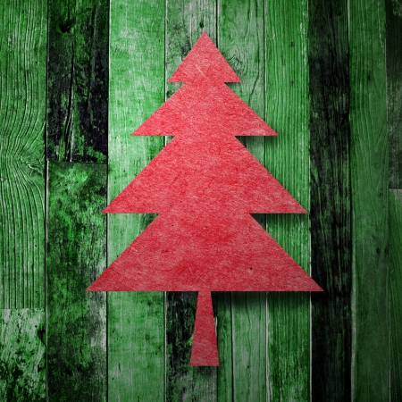 Red christmas tree on green wooden background