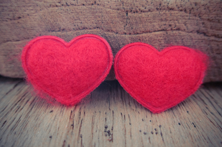 Red heart on wood background with vintage color