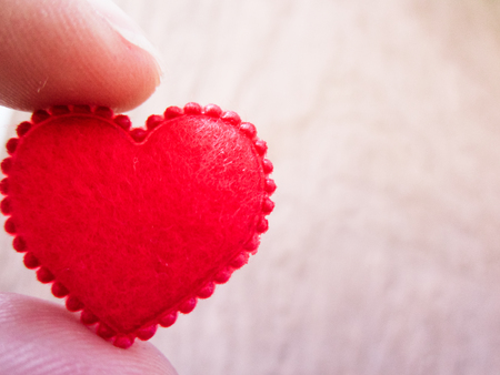 Red heart hold by finger