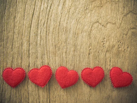 Many red hearts on wood background, vintage color Stock Photo