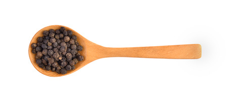 Wooden spoon and black peppercorn on white