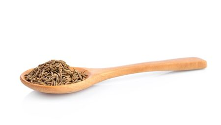 dried cumin seed or caraway in wooden spoon isolated on white background
