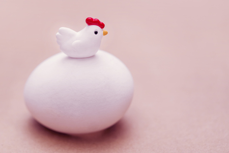 Little toy chicken in the eggshell  on a pink background Stock Photo