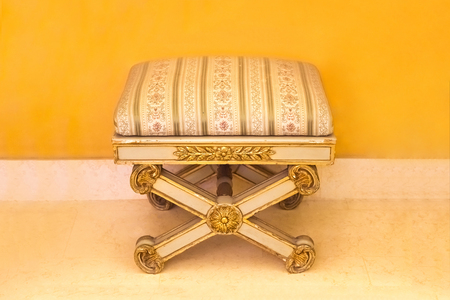 Classic retro foot stool with striped upholstery near the yellow wall
