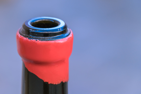 Neck of a opened wine bottle with a part of the red label; close-up