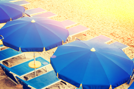 Blue empty sunbeds with umbrellas on the beach