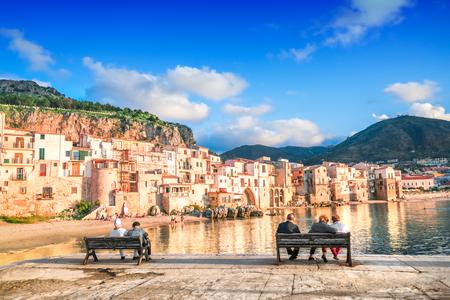 La gente si siede sulle panchine sul mare con una vista di Cefalù, Sicilia, Italia