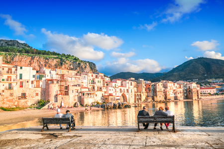 People sit on benches by the sea with a view of Cefalu, Sicily, Italy