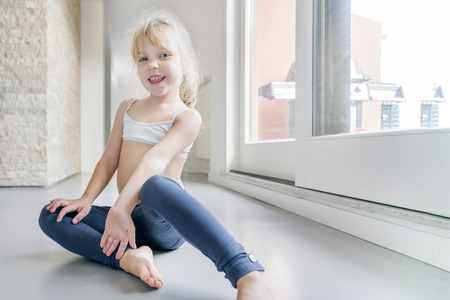 Happy little blond girl in white top and blue leggings sitting on the floor in the room