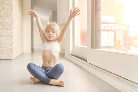 Little blond girl doing a yoga exercise in the sunny room