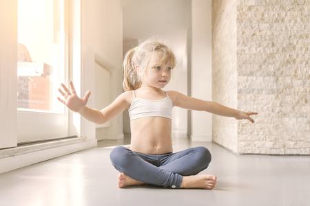 Little blond girl in white top and blue leggings doing a yoga exercise in the sunny room
